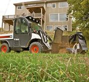 A Toolcat 5600 with a stump grinder attachment makes easy work of a large stump at a residence.