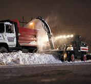 A Toolcat utility work machine uses a snowblower to throw snow into a truck early in the morning.