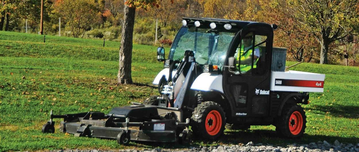 Toolcat 5600 and mower attachment cutting grass near a fence.