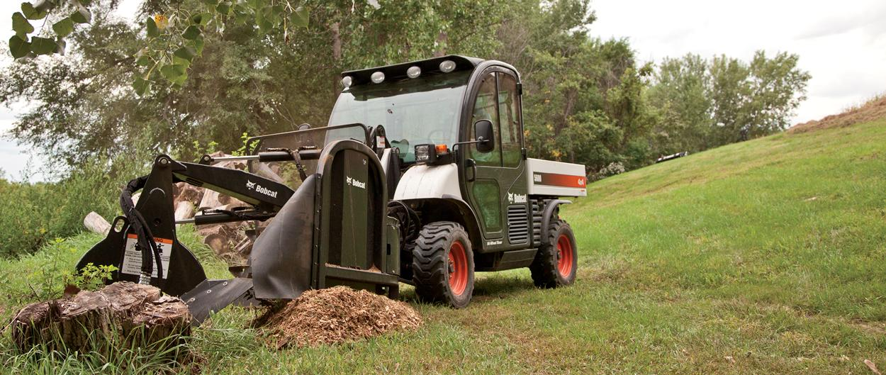 Toolcat 5600 utility work machine saws a stump using grinder attachment.