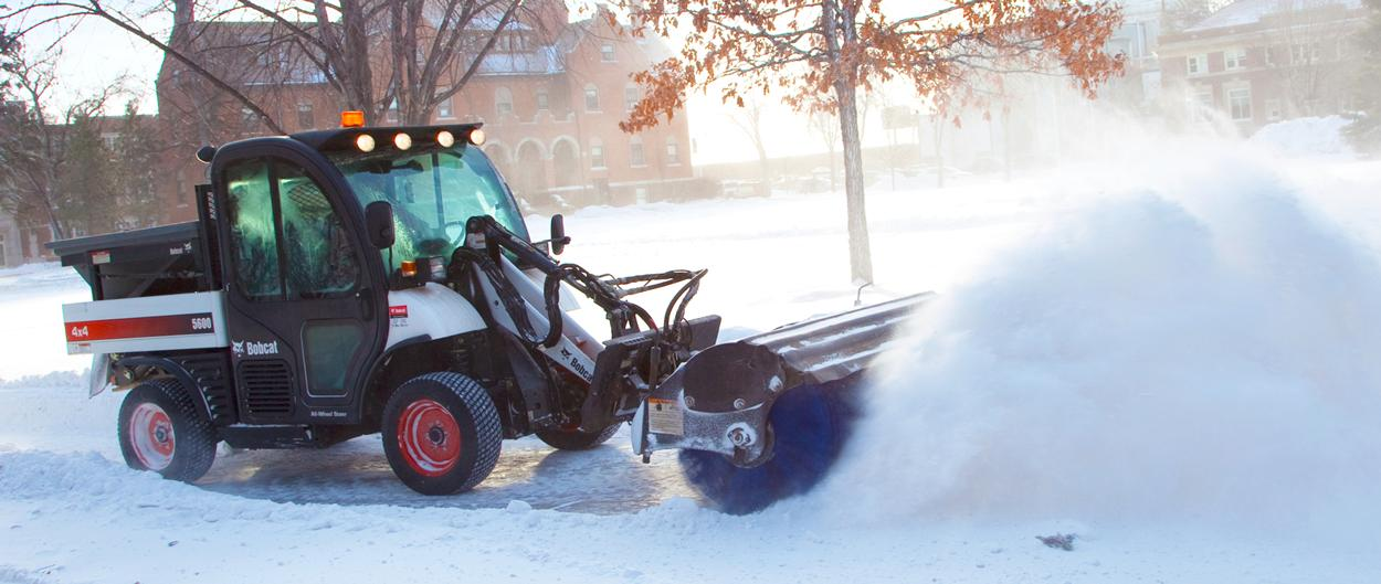 A Toolcat utility work machine clears a path with the angle broom, sweeping up a cloud of light, fluffy snow.