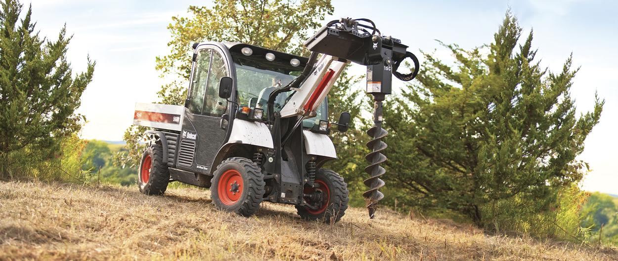 Toolcat 5600 uses auger attachments to dig holes for tree planting.