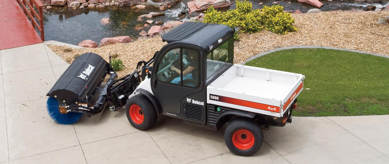 Toolcat 5600 utility work machine and angle broom attachment sweeping a college campus.