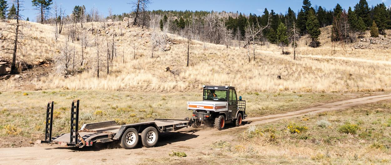 A Toolcat 5600 travels with a flatbed trailer down a dirt road.