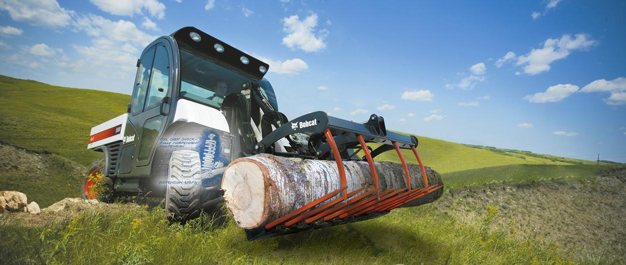 The suspension system is shown in an augmented photo of a Toolcat 5600 carrying a log up a hill with the utility grapple attachment.
