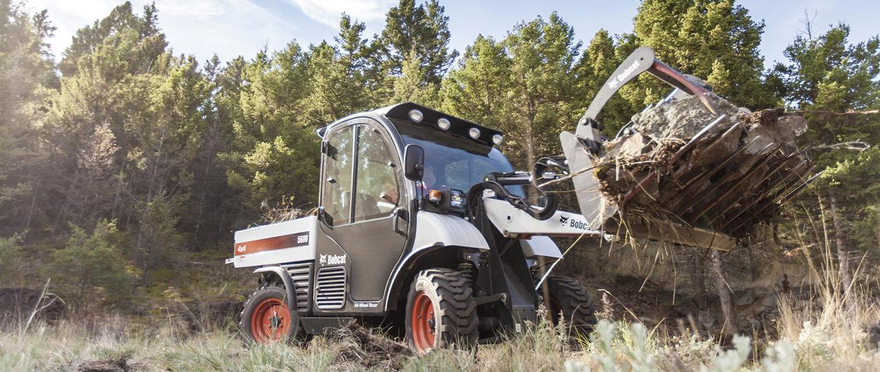 A Toolcat 5600 loaded with branches in a utility grapple attachment makes a tight turn through a grassy area.