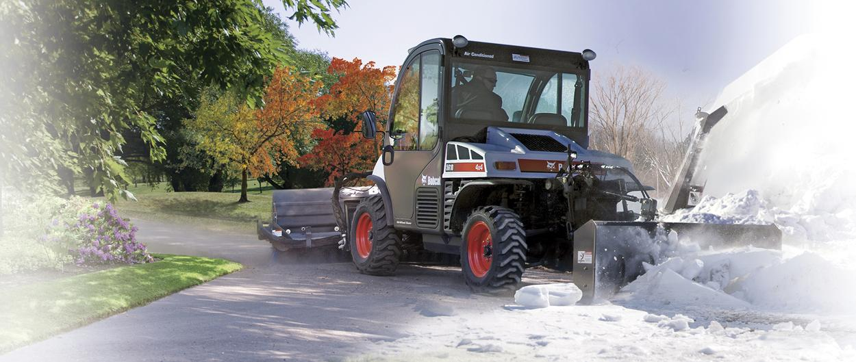 The chute of a snowblower attachment is angled to accurately place snow using rear remote hydraulics.