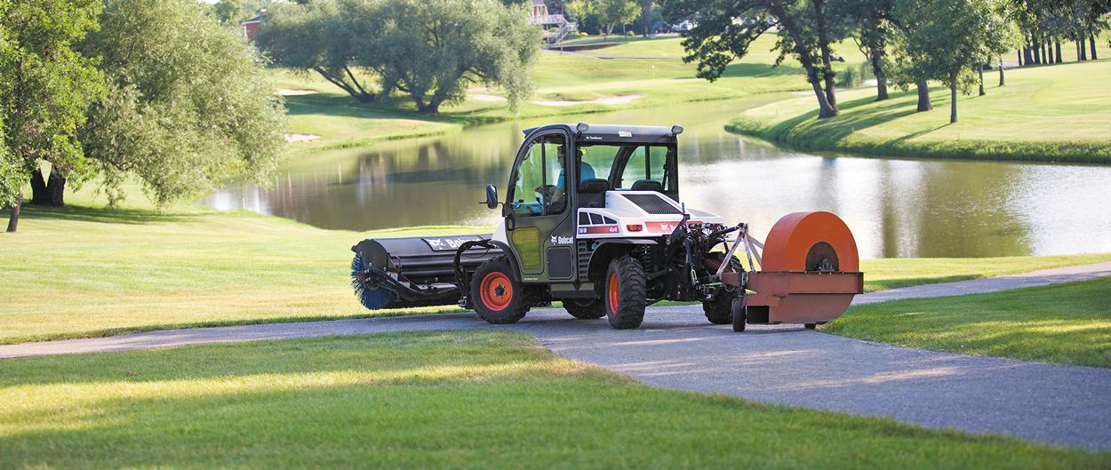 A Toolcat 5610 maneuvers around a tight golf course path while maintaining grounds.