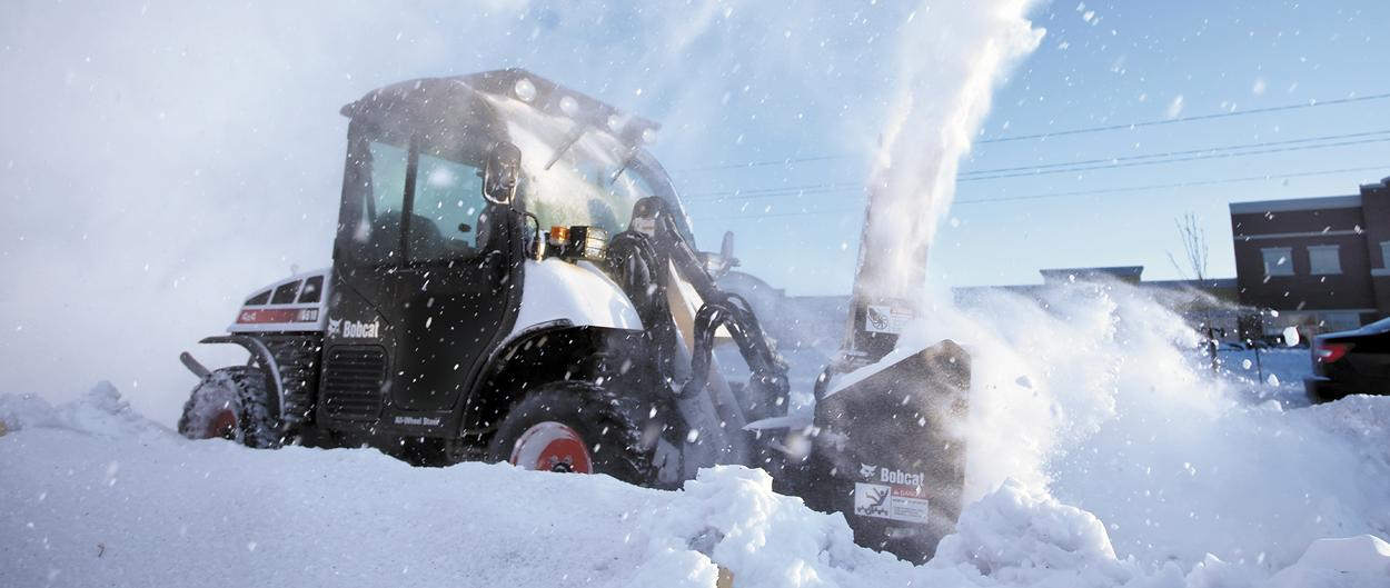 A Bobcat Toolcat 5610 throwing snow with a snowblower attachment.