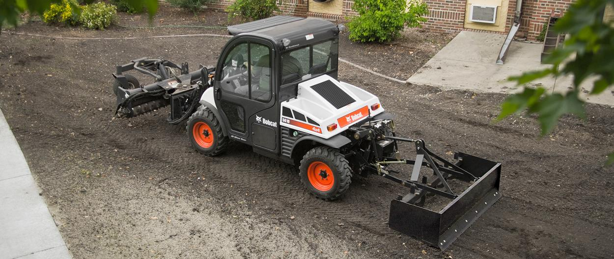 Toolcat 5610 with box blade implement and soil conditioner attachment prepares soil.
