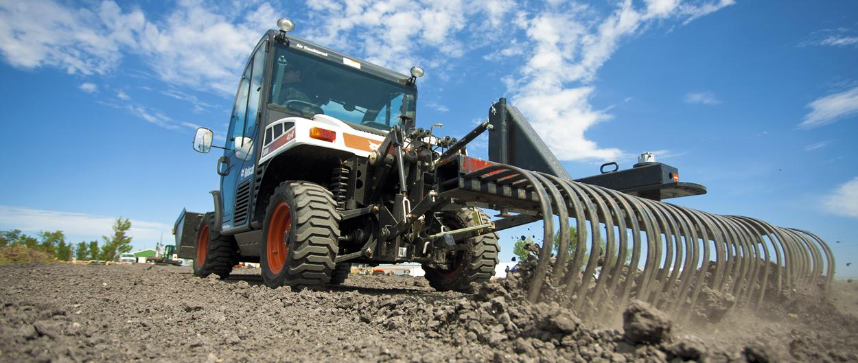 Toolcat 5610 with tine rake implement prepares soil for planting.