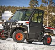 Bobcat 3600 utility vehicle with a modular cab parked on a snowy road.