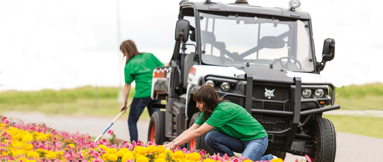 Grounds workers tend to flower beds on a college camps with a Bobcat 3400 UTV in the background.