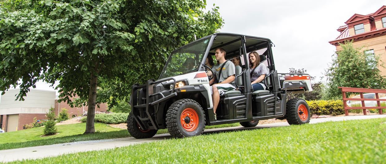 A Bobcat 3400XL utility vehicle with three passengers drives down a paved path at a college campus.