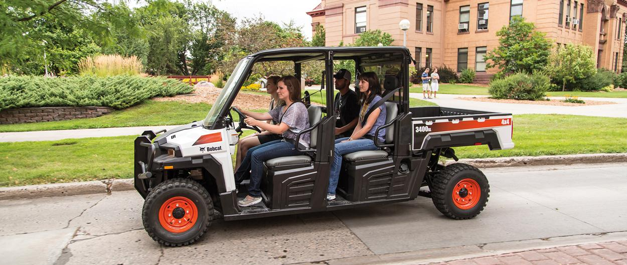 A Bobcat 3400XL utility vehicle with three passengers drives on a roadway in a college campus.