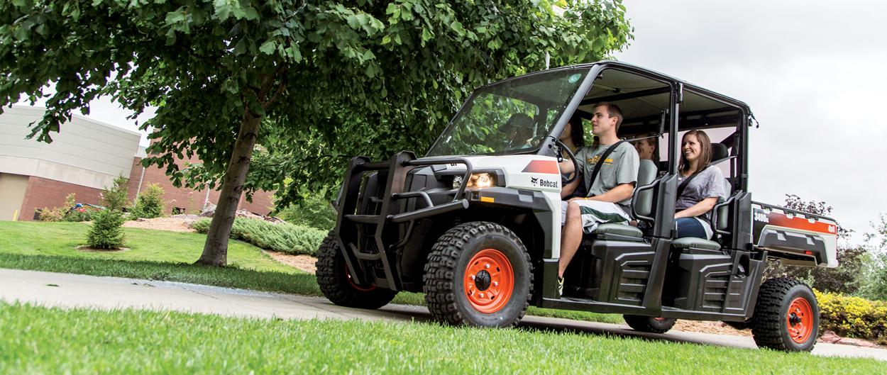 Bobcat 3400XL utility vehicle (UTV) with three passengers is driven on a college campus pathway.