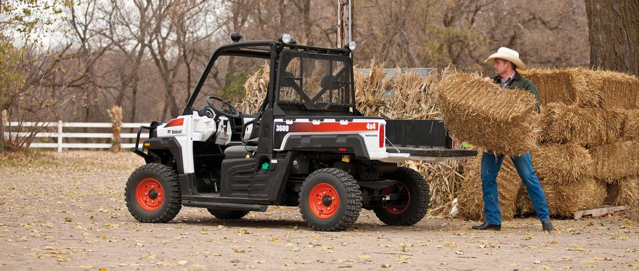 A farmer loads hay into the cargo box of the Bobcat 3600 utility vehicle.