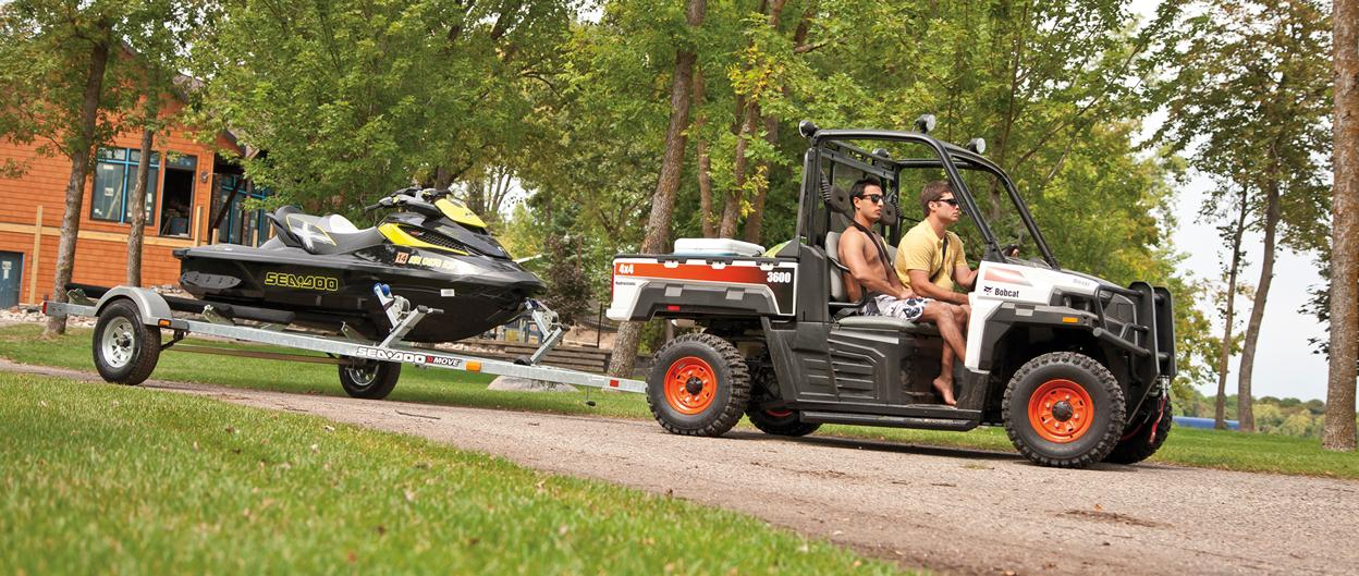 Young men use a Bobcat 3600 utility vehicle (UTV) to pull a jet ski at a lake cabin.