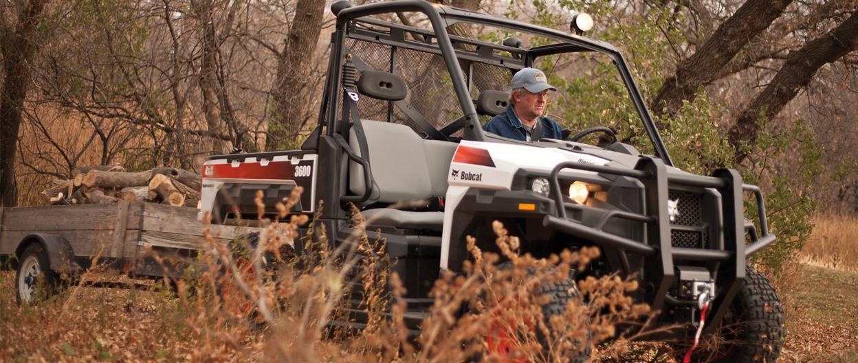 Bobcat 3600 UTV pulls trailer full of chopped wood.