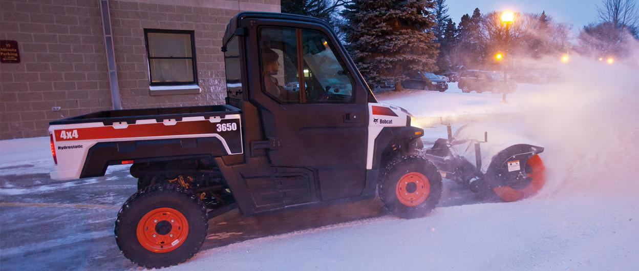 Bobcat 3650 with angle broom sweeps snow from a parking lot.