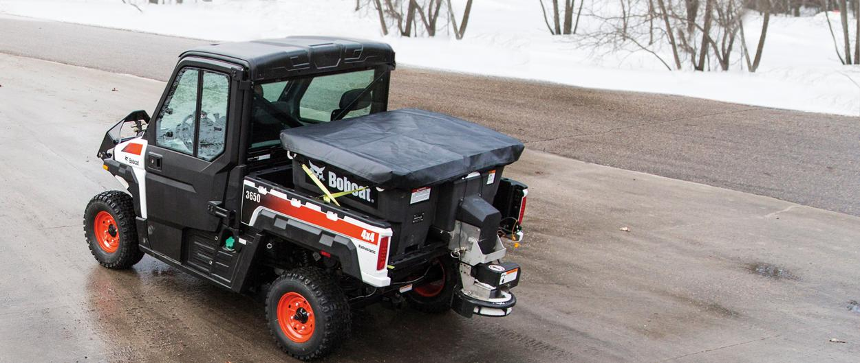 A Bobcat 3650 UTV uses a spreader attachment to dispense salt on an icy road.