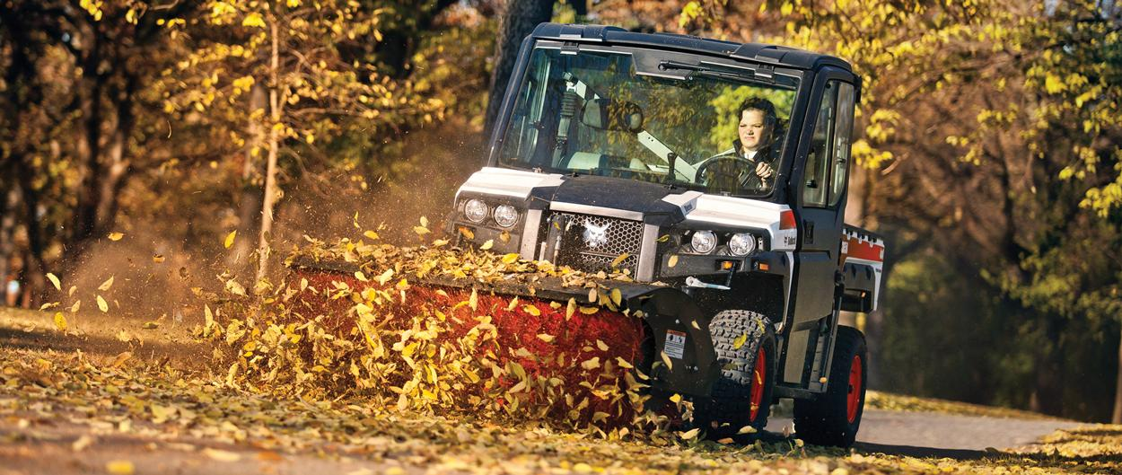 An angle broom attachment on a Bobcat 3650 utility vehicle is used to sweep leaves on a paved path.
