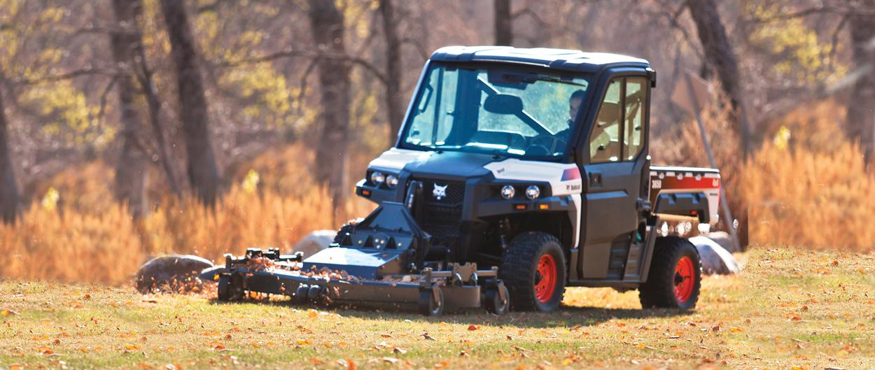 A Bobcat 3650 utility vehicle with mower attachment mows grass in the fall.