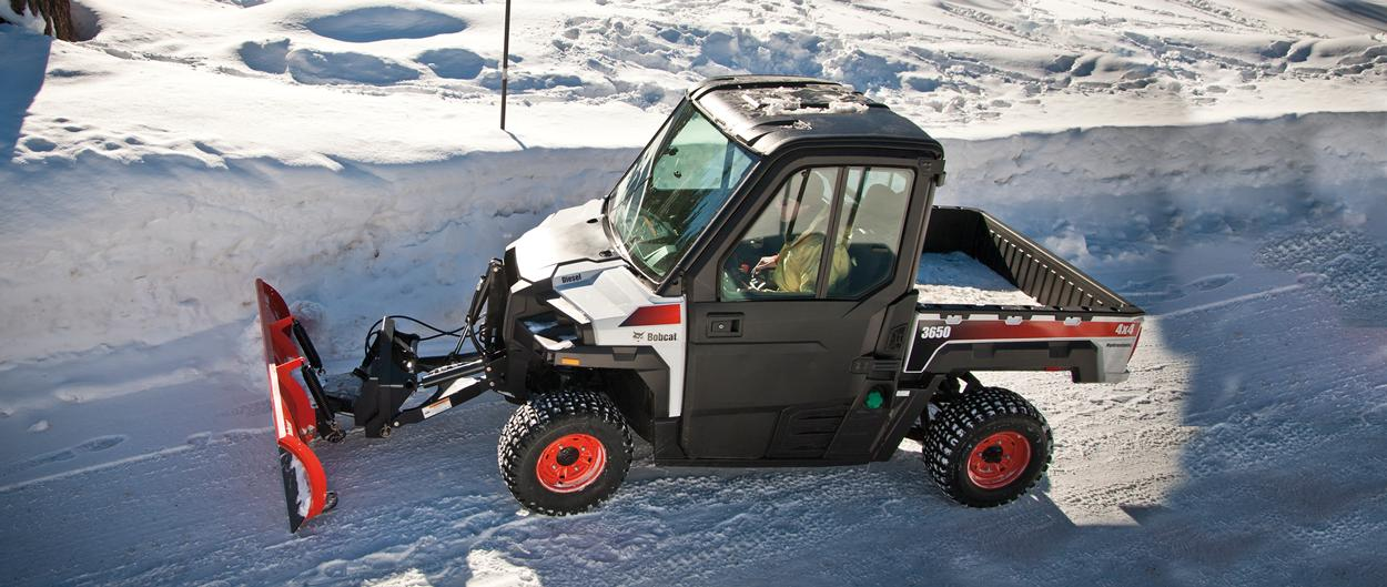Bobcat 3650 UTV with snow blade clears snow on a road.