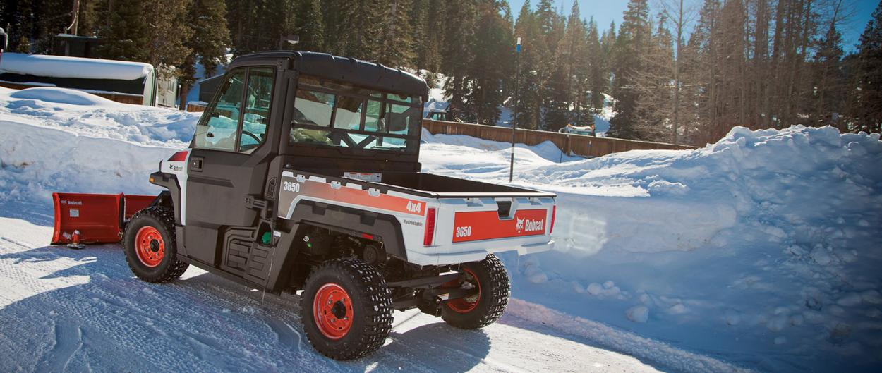 A Bobcat 3650 utility vehicle and snow blade clears recent snowfall from the edge of a road.