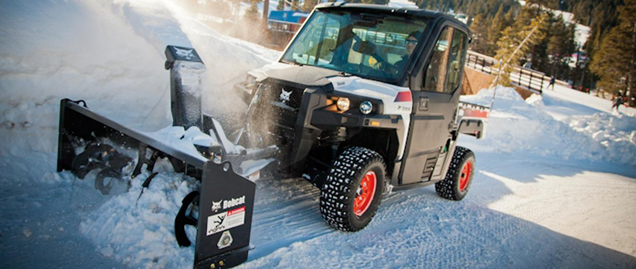 A 3650 utility vehicle with snowblower attachment clears snow on a mountain road.