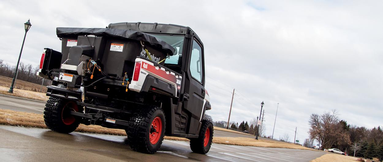 A Bobcat 3650 utility vehicle covers an icy path with salt and sand using a spreader attachment in the cargo box.