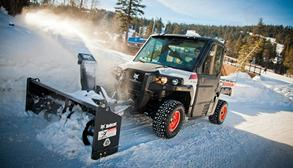 Bobcat 3650 utility vehicle with a snowblower attachment on a mountain road.