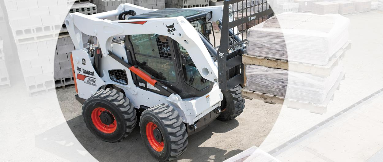 A Bobcat all-wheel steer loader with a pallet fork attachment.