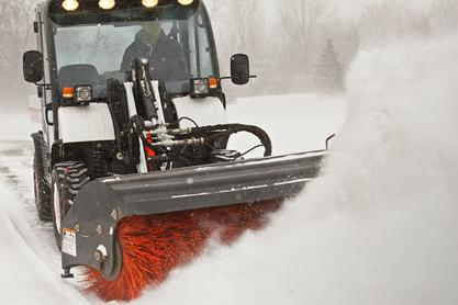 Bobcat angle broom attachment on a Toolcat 5600 machine sweeping snow with Angle Broom attachment.