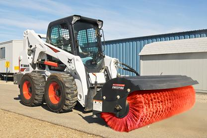 Bobcat angle broom attachment on a S650 skid steer loader sweeping a construction site with Angle Broom attachment.