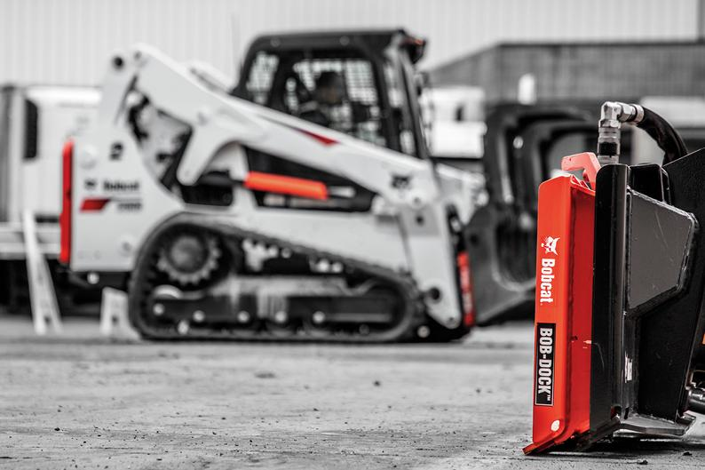 A Bob-Dock adapter sits in the foreground while a Bobcat T650 compact track loader with a Bob-Dock attachment system uses a grapple attachment in the background.