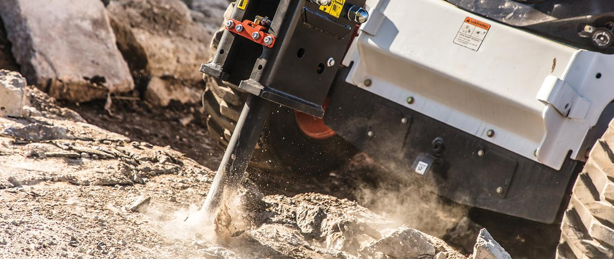 Demolition of reinforced concrete by a Bobcat nitrogen breaker attachment on a skid-steer loader.