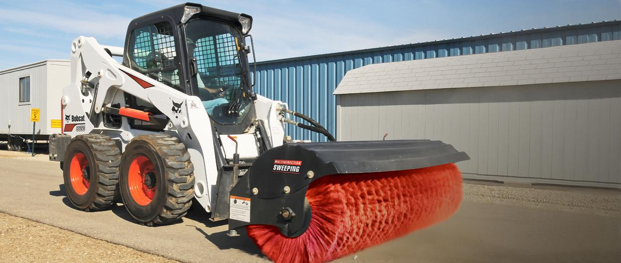 Bobcat skid-steer loader with angle broom attachment.