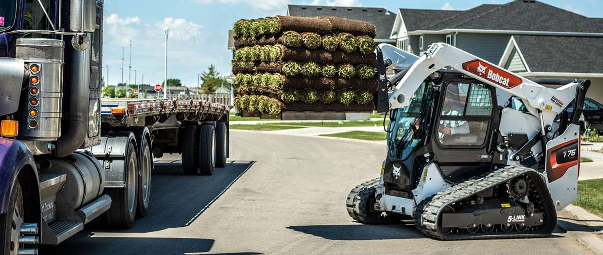 Bobcat T76 Compact Track Loader With Pallet Fork Attachment Loading Sod On To Truck Bed.