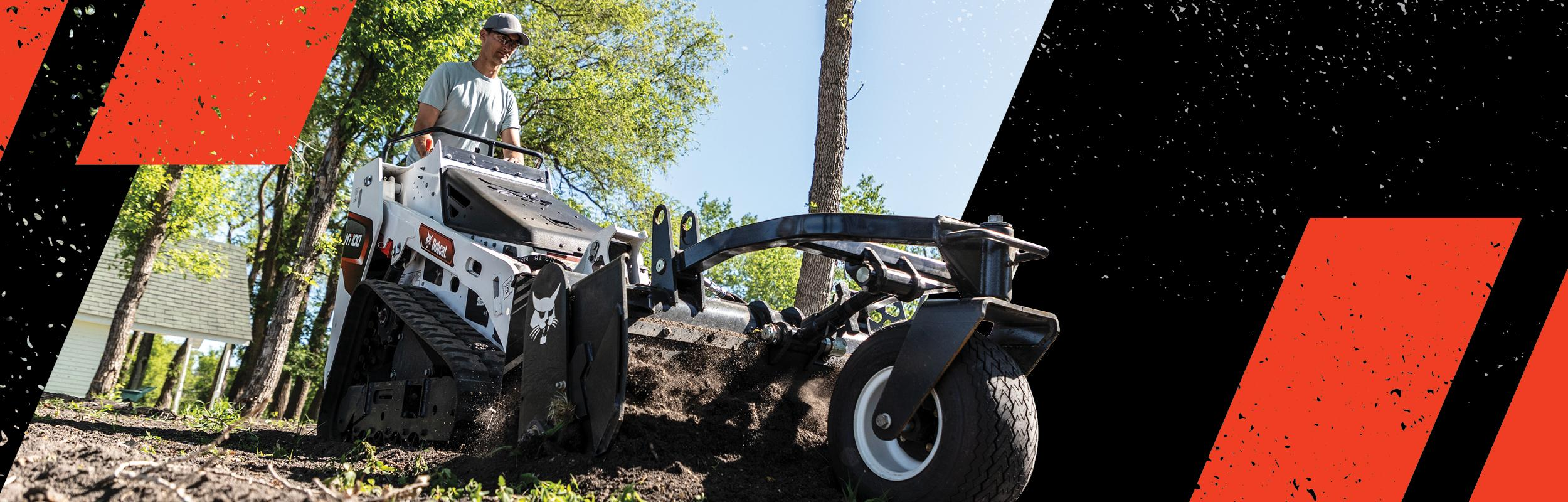 Operator Using A Bobcat MT100 Mini Track Loader With Box Blade Attachment To Move Dirt In Yard