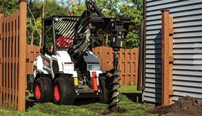 Operator Using A Bobcat L28 Small Articulated Loader With Auger Attachment To Drill Hole In Yard