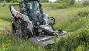 Operator Using A Bobcat T76 Compact Track Loader With Brushcat Rotary Cutter Attachment To Cut Heavy Grass And Weeds In Field