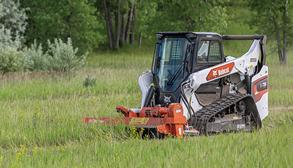 Compact Track Loader Operator Using Flail Cutter Attachment To Mow Overgrown Brush On Rural Property