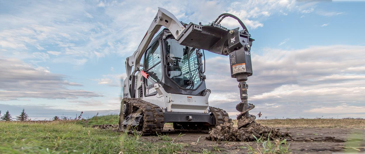 Bobcat T590 compact track loader hauls dirt in bucket.