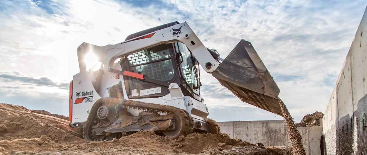 Bobcat T590 compact track loader backfills dirt by house foundation.