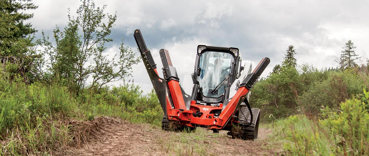 Bobcat T750 compact track loader moving with tree spade attachment.