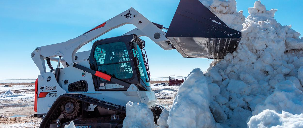 Bobcat T870 compact track loader lifting snow.