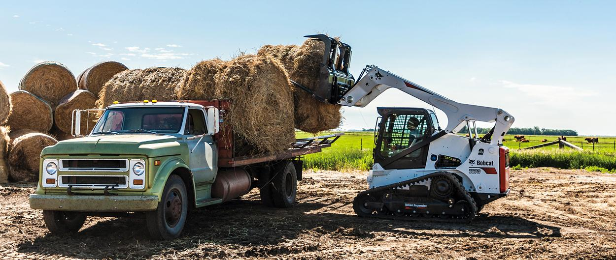 Bobcat T870 compact track loader and industrial grapple moving a round hay bale onto a flatbed truck.