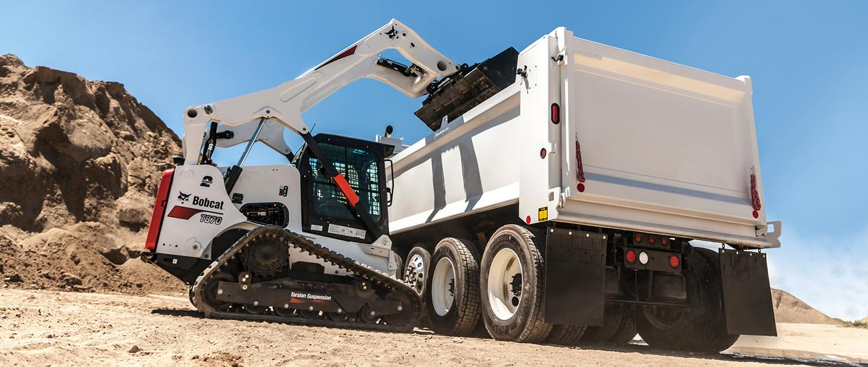 Bobcat T870 compact track loader lifts material into a high-sided truck.