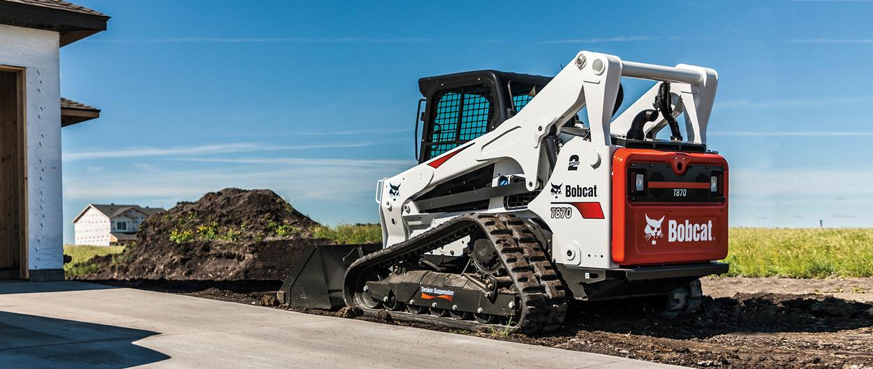 Bobcat T870 compact track loader and pushes dirt with a bucket attachment.